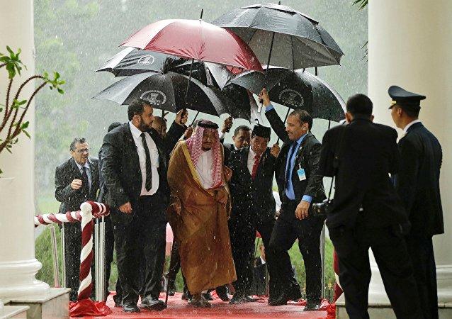 O rei da Arábia Saudita, Salman bin Abdulaziz e o presidente da Indonésia, Joko Widodo, caminham sob uma chuva forte no palácio presidencial em Bogor, 1 de março de 2017.