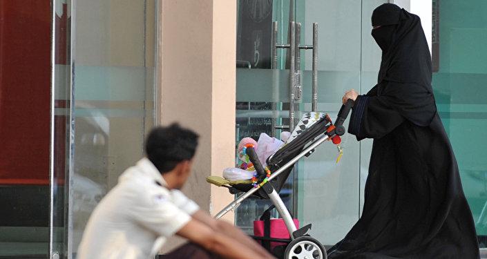 Uma mulher saudita passa por um trabalhador estrangeiro em 7 de novembro de 2013 em Riad.