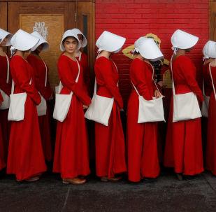 Mulheres vestidas como criadas promovem a telenovela Contos de Criada em Austin, EUA