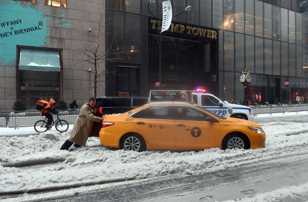 Carro atascado em neve no meio de uma rua em Nova York