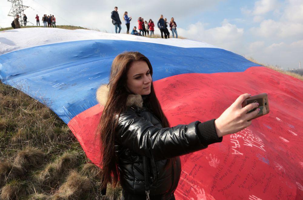 Menina tira selfie com enorme bandeira da Rússia durante festival em Simferopol
