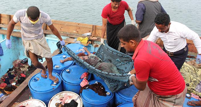 Pessoas carregam o corpo de um refugiado somali, morto em um ataque de helicóptero enquanto fazia uma travessia de barco na costa do Iêmen. 17 de março de 2017