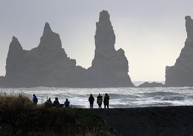 As pessoas andam na praia de areia negra em Vik, Islândia, perto do vulcão Katla