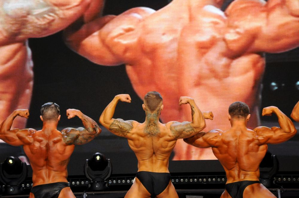 Os participantes estão demonstrando seus corpos musculares no palco do Campeonato aberto de fisiculturismo, fitness e desfile em biquíni na sala do Palácio da Cultura dos Trabalhadores Ferroviários em Chita, região de Transbaikal, Rússia