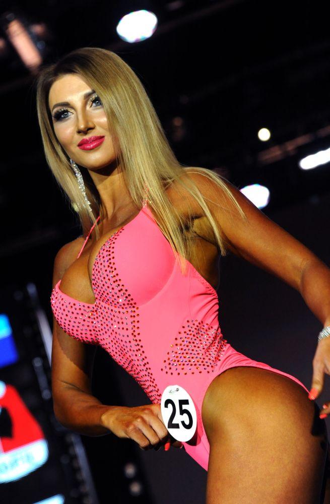 Uma participante com um biquíni rosa exibe seu corpo musculoso durante o Campeonato aberto de fisiculturismo, fitness e desfile em biquíni na sala do Palácio da Cultura dos Trabalhadores Ferroviários em Chita, região de Transbaikal, Rússia