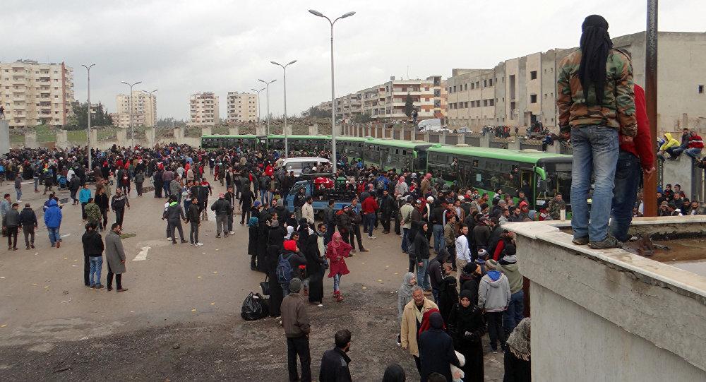 Combatentes da oposição e suas famílias se reúnem, enquanto se preparam para subir a um ônibus, antes da evacuação do bairro rebelde de Waer, na cidade de Homs, em 18 de março de 2017