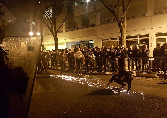 Manifestantes usam velas para soletrar a palavra violência diante de uma fila de policiais no 19º distrito de Paris - 27 de março de 2017