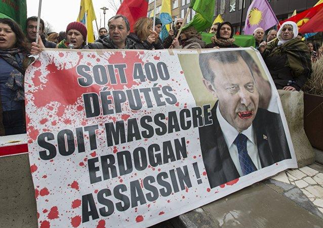 Manifestantes curdos exibem uma foto do presidente turco, Tayyip Erdogan, durante um protesto em frente a uma cúpula UE-Turquia, 7 de março de 2016