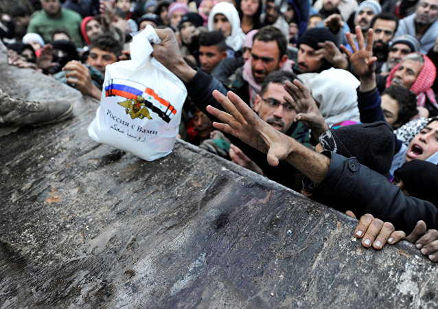 Syrians that evacuated eastern Aleppo, reach out for Russian food aid in government-controlled Jibreen area in Aleppo, Syria November 30, 2016.