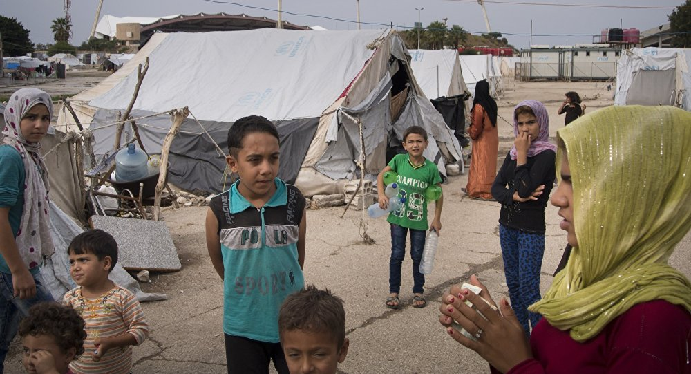Refugees stand at a camp in Latakia, Syria