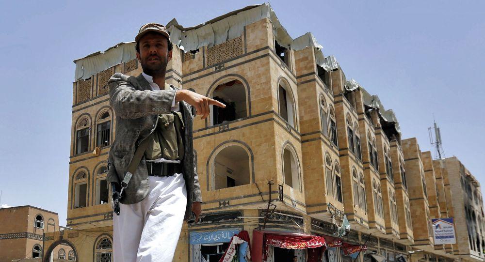 Um homem indica ao fotógrafo as consequências de um ataque aéreo da coalizão saudita no Iêmen (foto de 2015)