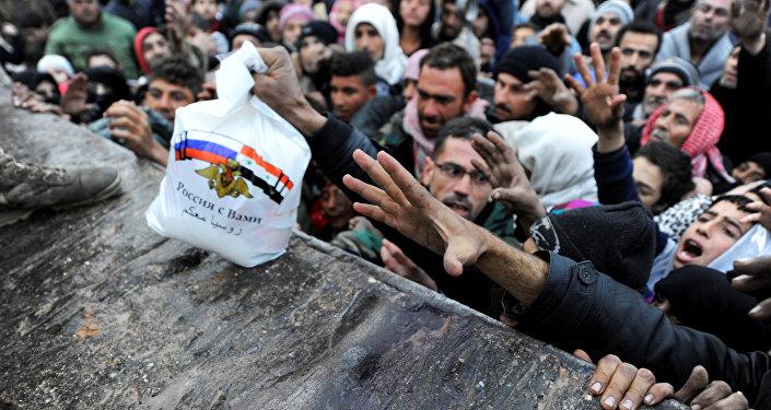 Sírios evacuados de Aleppo Oriental recebem alimentos doados pela Rússia em Jibreen (arquivo)