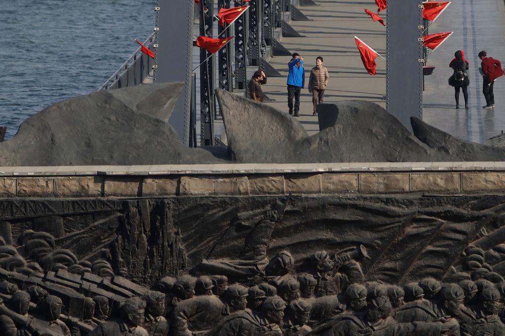 Turistas passeiam na Ponte da Amizade Sino-Coreana, 13 de abril de 2017