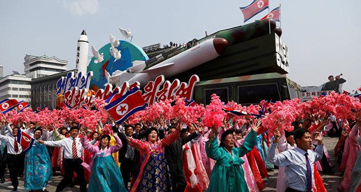 Cidadãos norte-coreanos cumprimentam Kim Jong-un durante a a parada militar comemorativa do 105º aniversário de Kim Il-sung, em 15 de abril de 2017