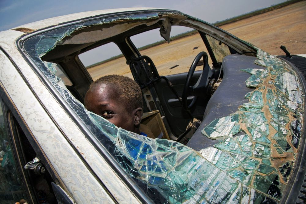 Menino brinca em um carro destruído na sequência das ações militares no Sudão do Sul