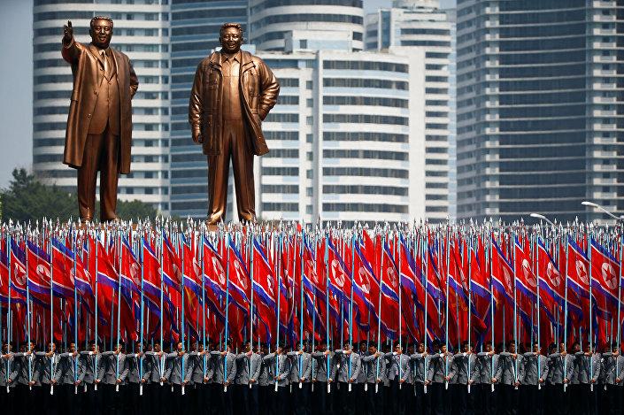 Pessoas carregam bandeiras em frente dos monumentos de Kim Il-sung e Kim Jong-il durante a parada militar comemorativa dem 15 de abril de 2017