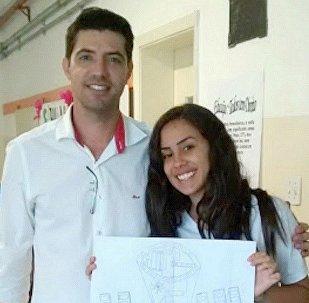 Professor David Cristiano de Almeida Postelhone e a estudante Isabela com o desenho que recebeu a menção honrosa da Nasa