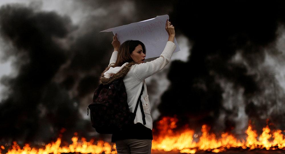 Uma manifestante mostra seu cartaz nas primeiras horas da greve geral de 28 de abril de 2017 em Brasília