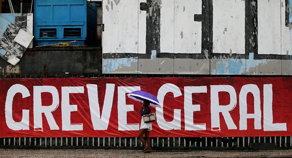 Uma mulher passa na frente de uma parede com a inscrição Greve Geral no Rio de Janeiro em 28 de abril de 2017