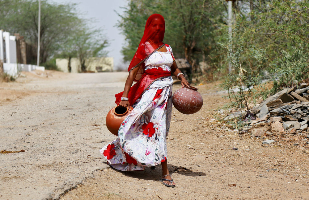 Uma mulher com potes de barro no estado do Rajastão, Índia