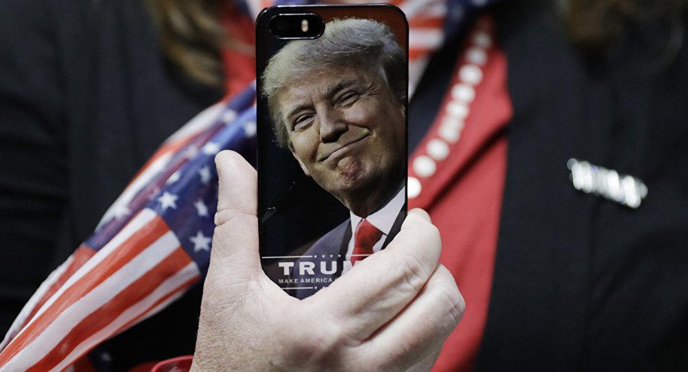 Mulher segura celular com a foto de Donald Trump