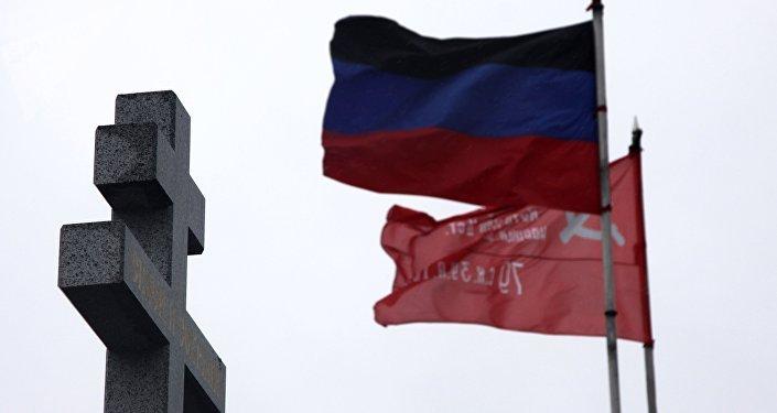 Bandeira da República Popular de Donetsk é vista hasteada no complexo memorial de Saur-Mogila em 9 de maio de 2017, junto a uma cruz cristã ortodoxa
