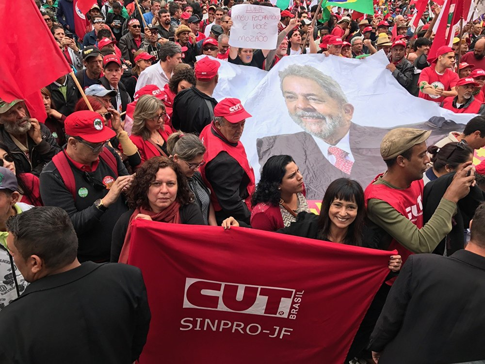 Membros da Central Única dos Trabalhadores perto de uma grande foto do ex-presidente Lula na praça Santos Andrade, em Curitiba