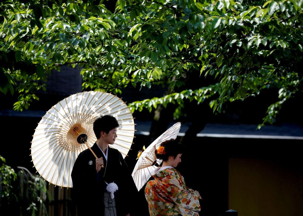 Casal vestido de quimonos tradicionais japoneses participa de sessão de fotos em Kyoto, Japão