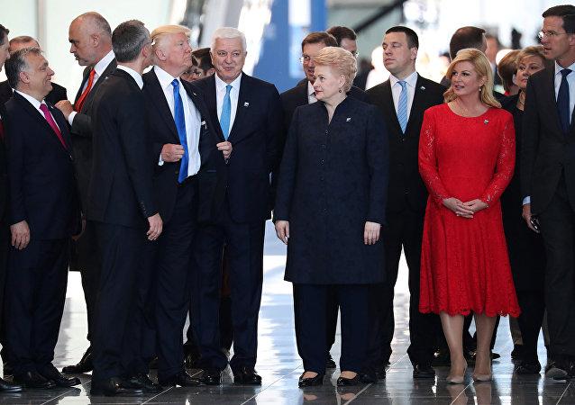 Donald Trump ajeita seu terno após empurrar o primeiro-ministro de Montenegro, Dusko Markovic