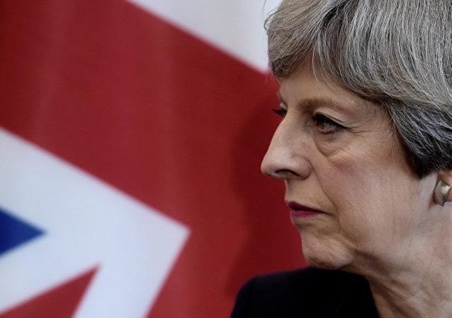 A primeira-ministra britânica, Theresa May, escuta o presidente francês durante uma reunião bilateral na Cúpula do G7 em Taormina
