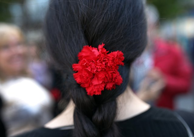 Jovem usa um cravo nos cabelos durante a celebração dos 40 anos da Revolução dos Cravos