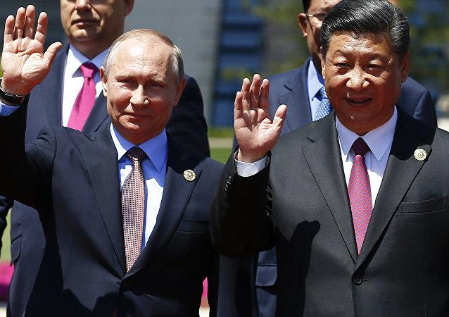 Presidentes Vladimir Putin e Xi Jingping acenam durante evento em Pequim