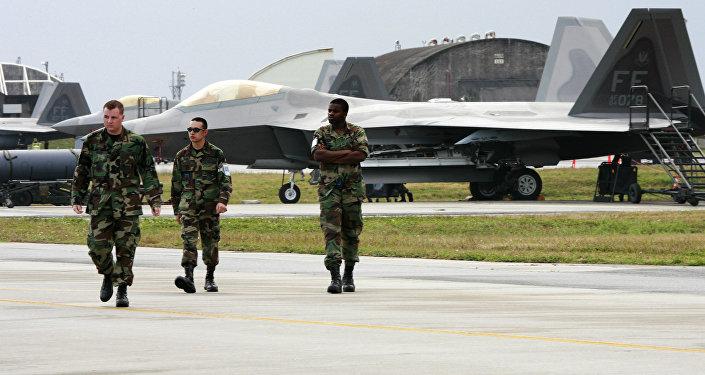 Militares norte-americanos junto a caças F-22A Raptor da Força Aérea dos EUA na base militar estadunidense , na ilha de Okinawa, Japão