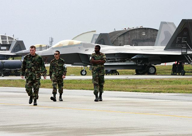 Militares norte-americanos junto a caças F-22A Raptor da Força Aérea dos EUA na base militar estadunidense de Kadena, na ilha de Okinawa, Japão