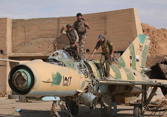 Combatentes das Forças Democráticas da Síria (FDS) posando com um avião destruído no aeroporto militar de Tabqa após o terem reconquistado ao Daesh, em 9 de abril de 2017