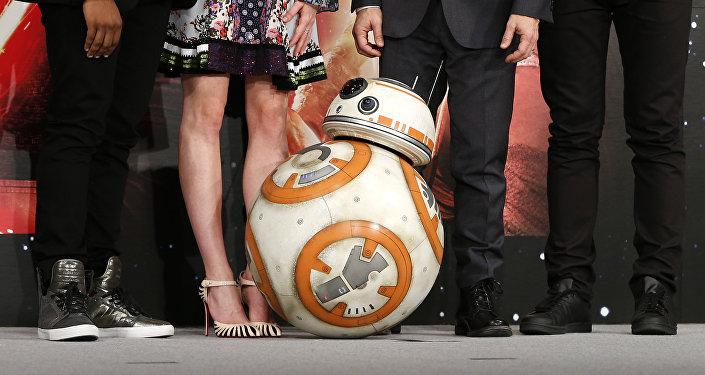 O robô BB-8 posando com atores e diretor durante conferência de imprensa do filme Star Wars: O Despertar da Força