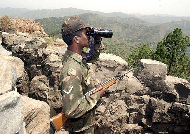 Um soldado indiano olhando pelo binóculo a 200 km da Linha de Controle que separa Índia e Paquistão