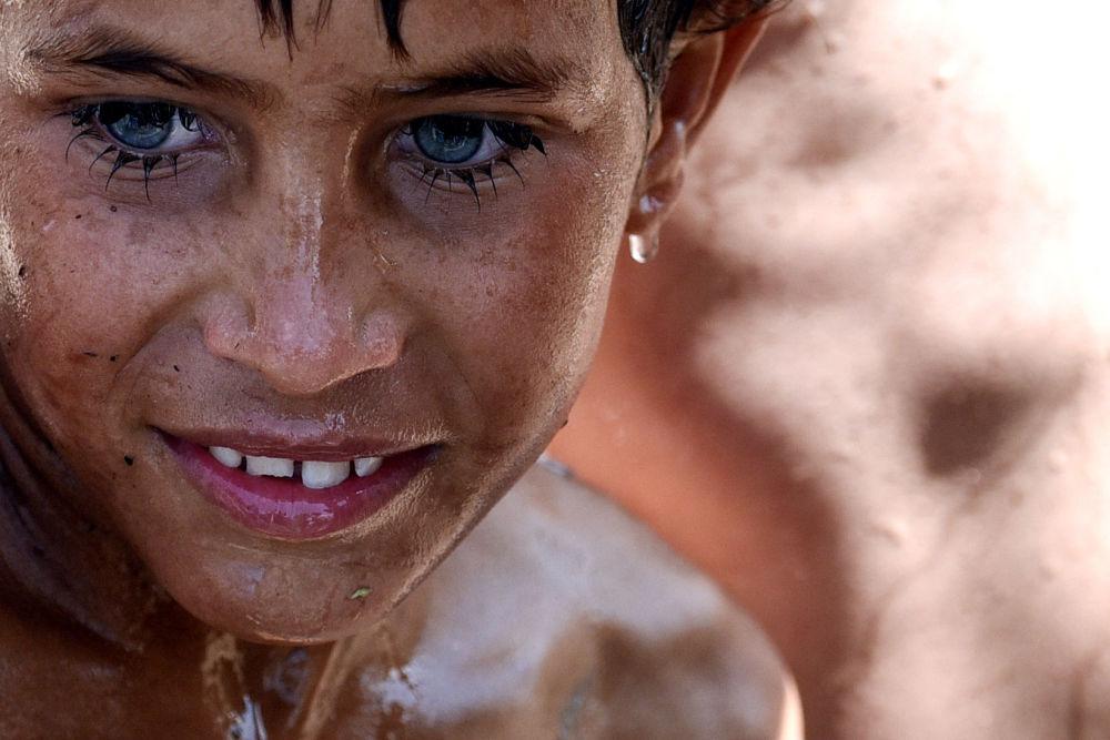 Menino iraquiano toma banho no campo de refugiados entre Arbil e Mossul