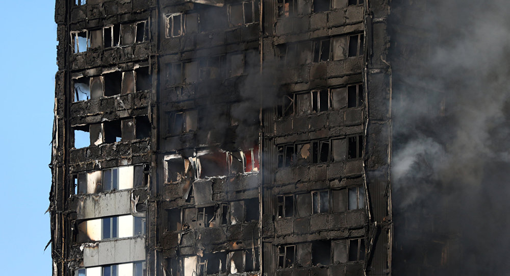 The burnt facade of a tower block is seen as firefighters tackle a serious fire at Latimer Road in West London, Britain June 14, 2017