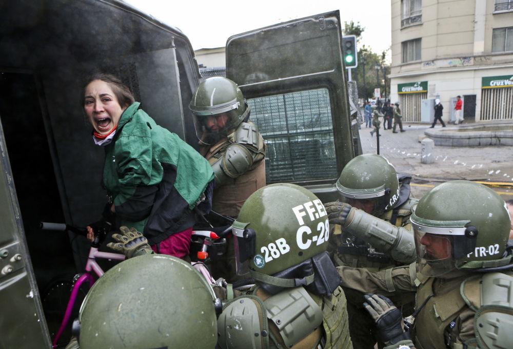 Participante de um protesto sendo detida em Santiago, capital chilena