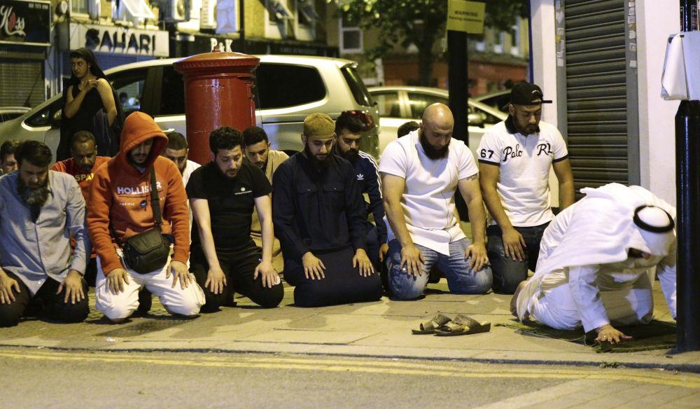 Pessoas rezam no local do incidente em Londres, onde um carro atropelou as pessoas em 19 de junho