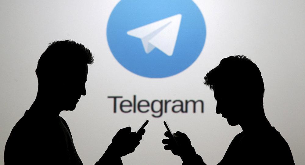 Dois homens, usando seus smartphones, estão em frente ao logotipo do Telegram
