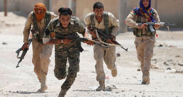 Milicianos curdos do YPG correm nas ruas de Raqqa
