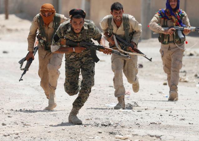 Milicianos curdos das YPG correm nas ruas de Raqqa (foto de arquivo)