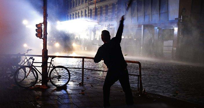 Manifestante joga uma garrafa contra a polícia de choque durante manifestações na cúpula do G20 em Hamburgo