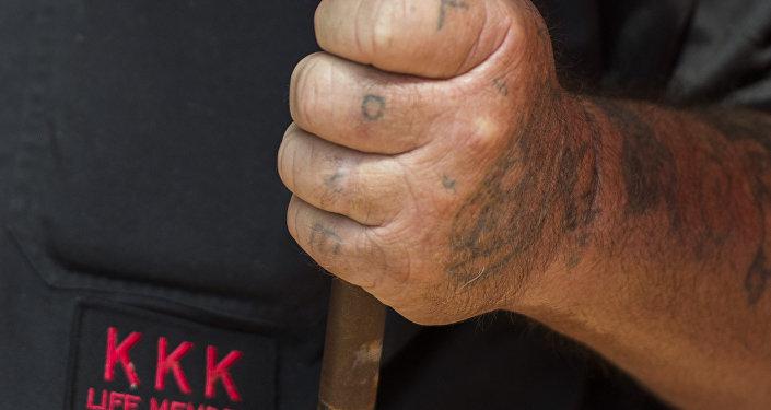 Membro do KKK com a palavra amor tatuada nos dedos