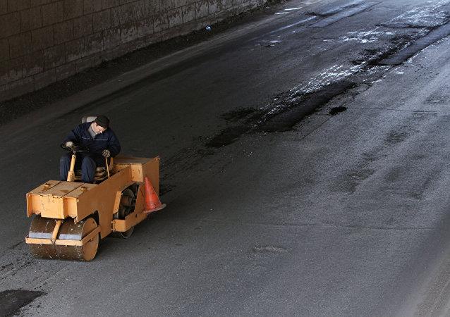 Operário asfalta rodovia na Rússia, foto de arquivo