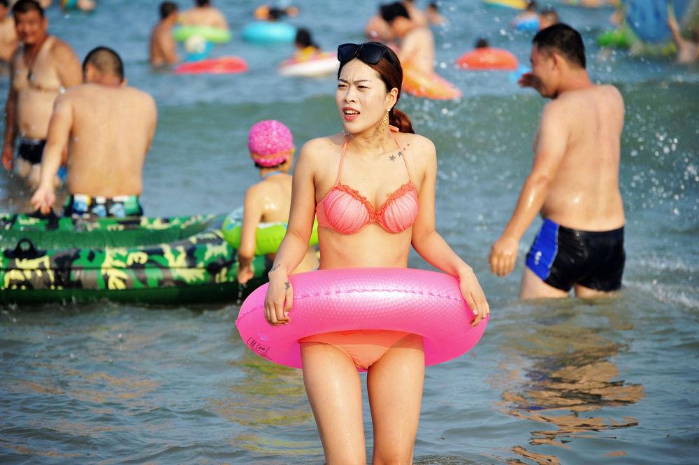 Mulher chinesa na praia em Qingdao, província de Shandong, China