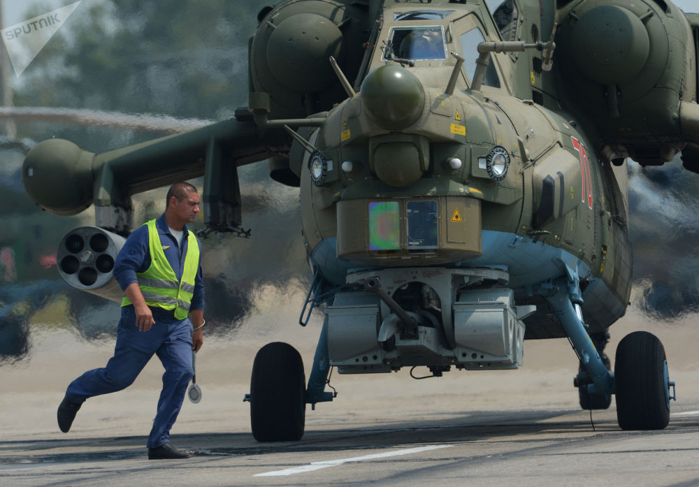 Técnicos em manutenção de aeronaves preparam helicóptero Mi-28 para voo no aeródromo Chernigovka, região de Primorie, Rússia