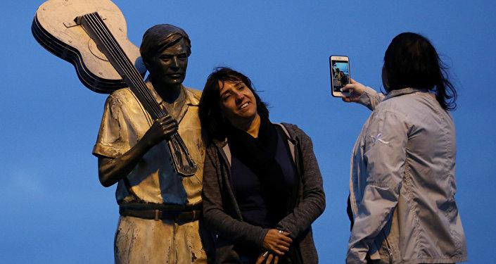 Mulher tira foto ao lado da estátua do músico Tom Jobim